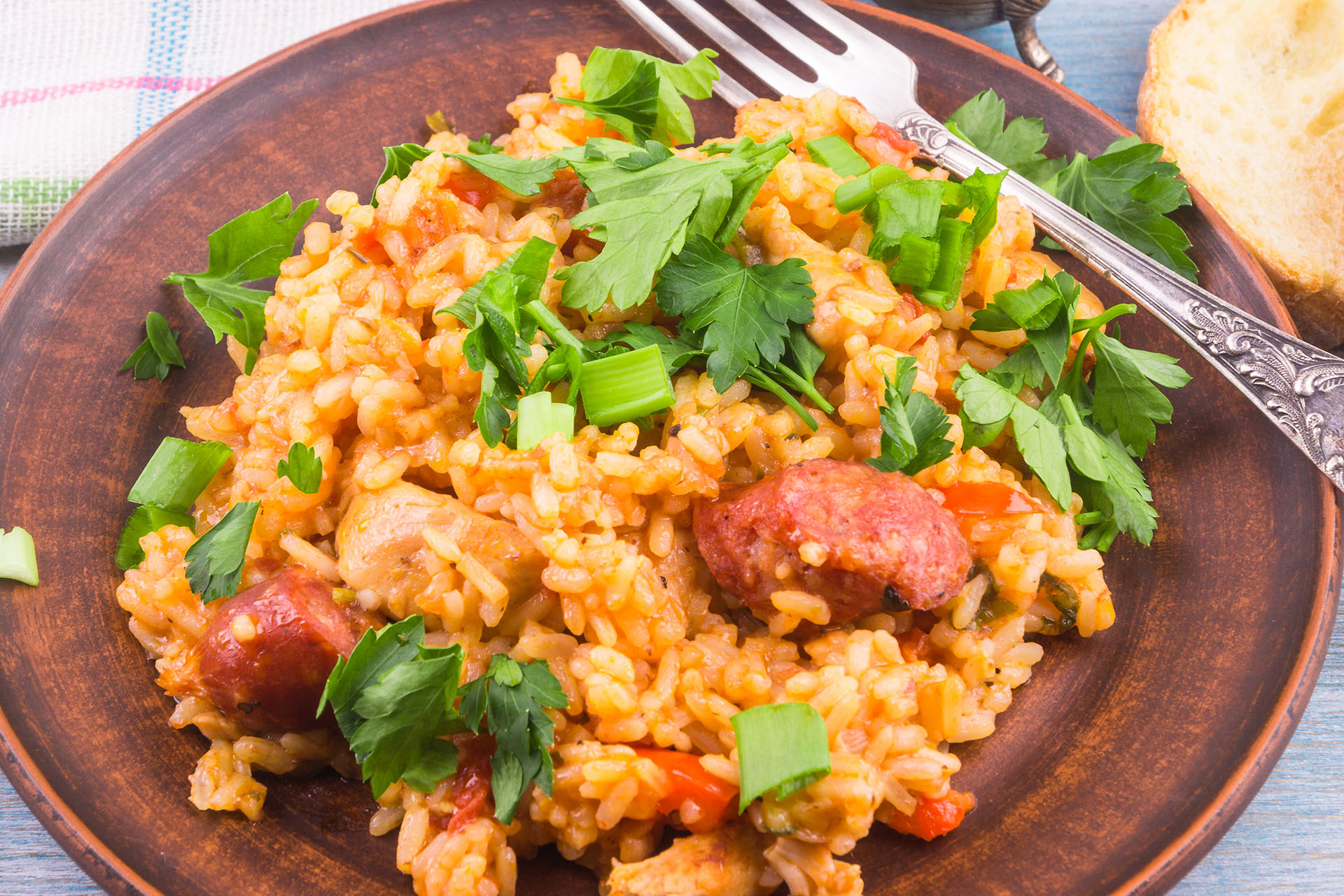 Traditional American New Orleans Jumbalaya with rice, chicken and sausages, on a clay plate, sprinkled with chopped parsley, closeup, top view.